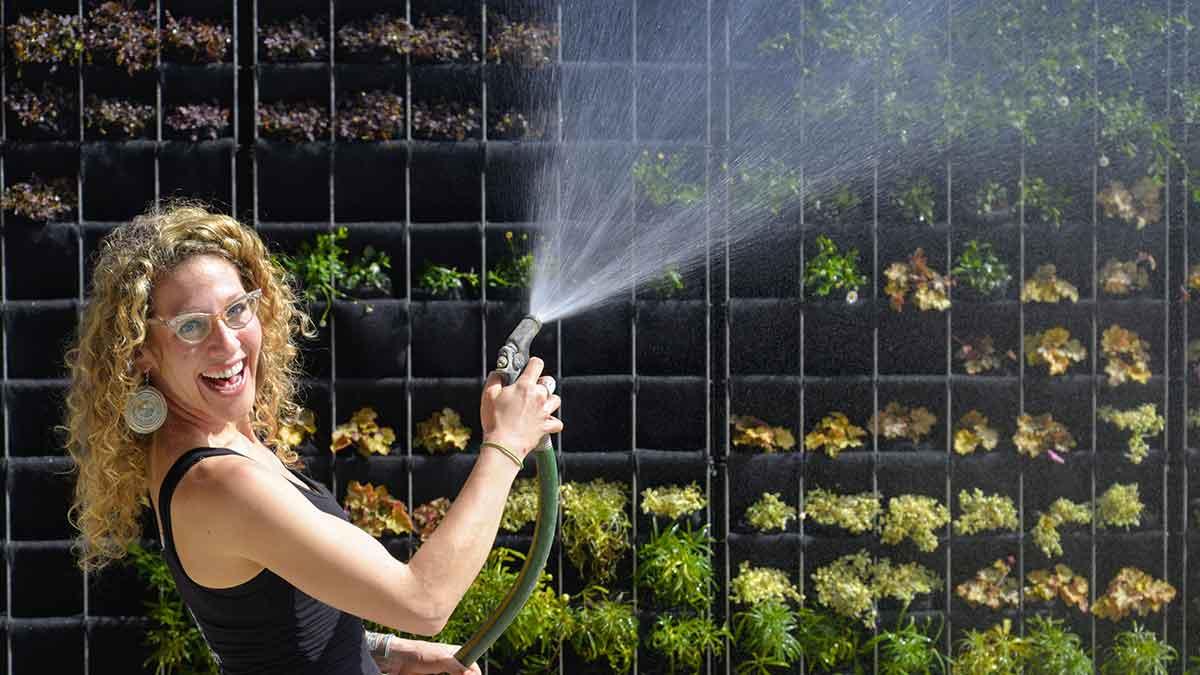 Amanda Goldberg of Planted Design hosing her Florafelt Pro System vertical garden.